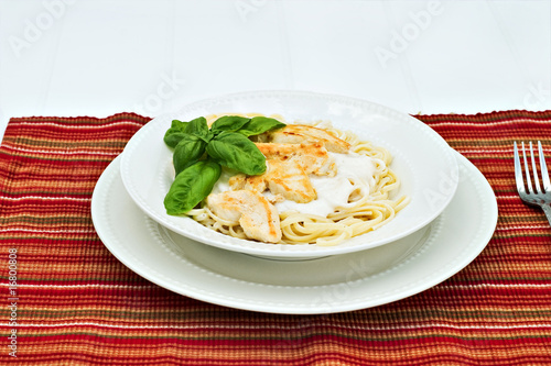Chicken alfredo with basil on a white table.