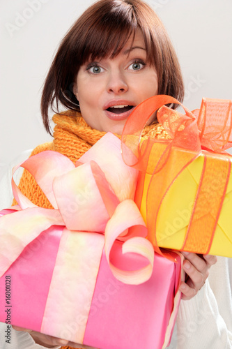 Portrait of young woman looking surprised holding gifts
