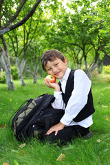 schoolboy with backpack and apple outdoors