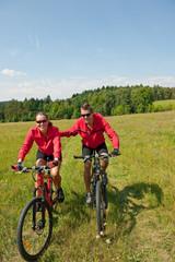 Sportive couple riding mountain bike in meadow