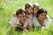 homme et femme avec enfants couchés dans l'herbe