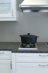 A very neatly clean kitchen with a casserole pot on the stove