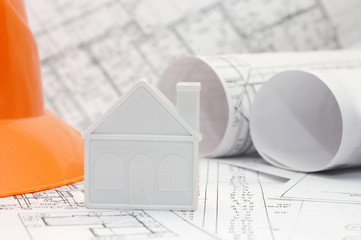 Close-up of toy house model on blueprints with helmet near by