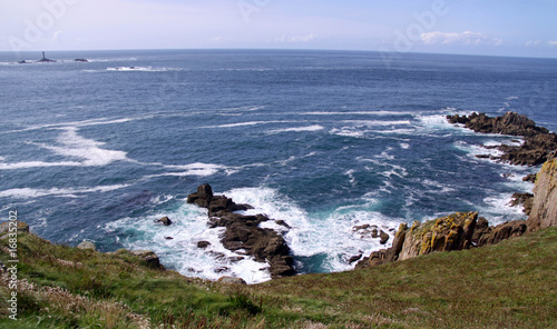 View of light house / lighthouse, sea, rocks Lands End, UK