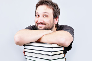 A young nice male is smiling on books