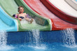 The boy slides a waterslide.