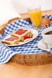 Homemade breakfast on wicker tray with checked teacloth poster