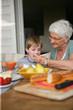 femme senior donnant à manger à un petit garçon