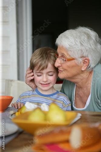 Portrait d'une femme senior et d'un petit garçon assis à table