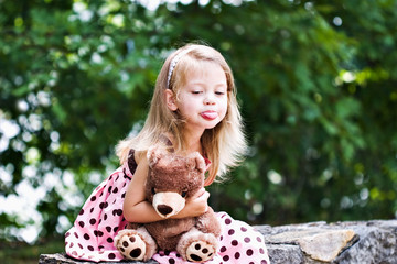 Child holding her teddy tightly and sticking out her tongue.