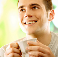 Young happy smiling man drinking coffee, outdoors