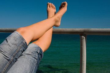 A pair of relaxing feet on the railing of a boat at sea