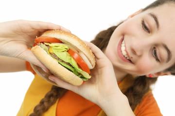 adolescente mange un hamburger