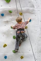 Kind beim Klettern an einer Kletterwand