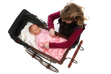 young girl looking down at baby doll in antique carriage