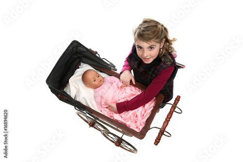young girl lifting doll from antique baby carriage