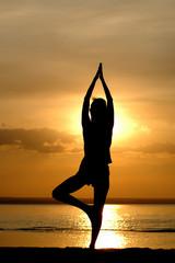Silhouette of the women meditate on sundown
