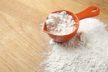 Measuring Cup with Flour on Cutting Board