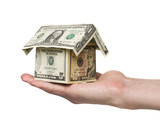 hand holding a small house built out of dollar bills