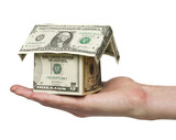 Man holding a small house built out of dollar bills