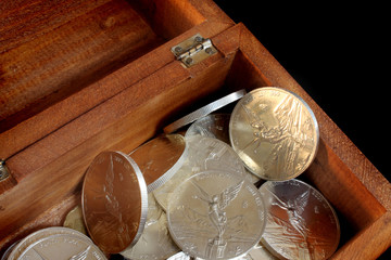 mexican fine silver coins in wooden chest