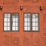 two old multipanel windows in a terracotta colored brick and woo poster