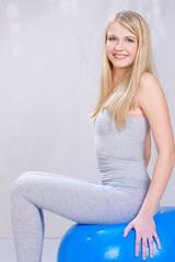 Pretty young blond hair girl seating on blue pilates ball