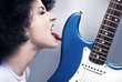 Beautiful rock-n-roll girl licking a guitar