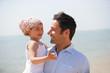 homme portant une petite fille souriante dans ses bras