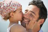 Portrait d'une petite fille embrassant un homme sur la joue