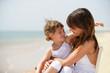 petite fille assise sur les genoux d'une femme au bord de la mer