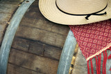 woven rug and straw hat on aged wine barrel