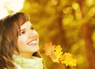 Beautiful romantic brunette with golden autumn leaf close-up por