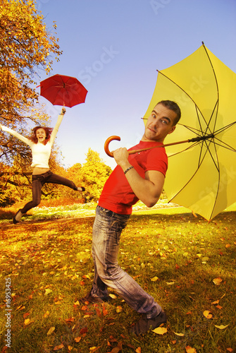 Funny couple with umbrellas on autumn background (focus on a guy
