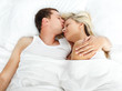 Boyfriend kissing her girlfriend in bed