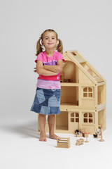 Young girl standing with dolls house 1