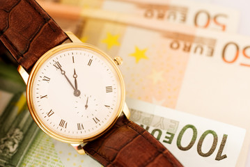 Golden watch on Euro banknotes