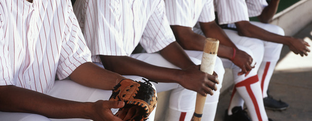 Baseball players sitting in dugout