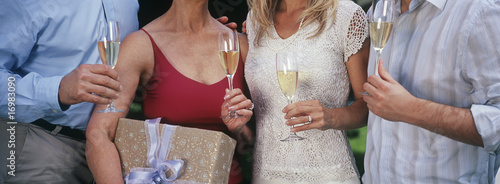 Young woman holding present, with friends drinking champagne, mid section
