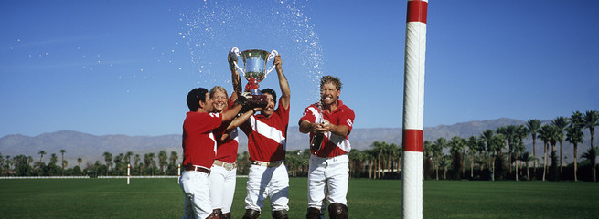 Polo team celebrating with trophy on field