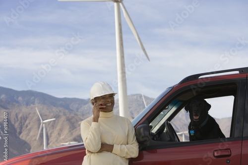 Mature woman by truck at wind farm