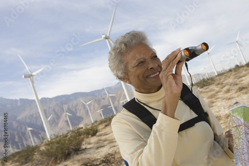 Mature woman with binoculars by wind farm