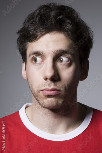 Young man in red top looking sideways