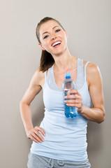 Sportlich lachende Frau hält Wasserflasche