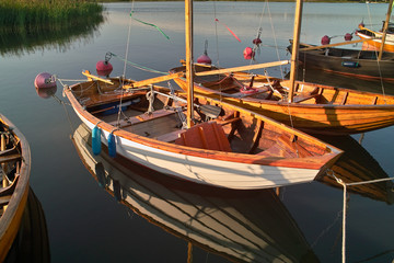 Wooden sailing boats at sunset, reflected in the quiet water