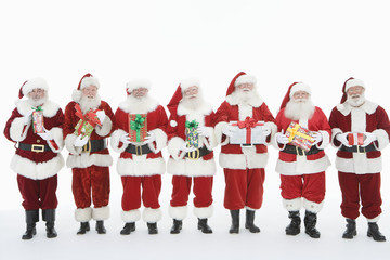 Group of men dressed as Santa Claus holding gifts