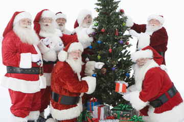 Group of men dressed as Santa Claus decorating Christmas tree