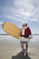 Father Christmas stands with a surfboard at the beach