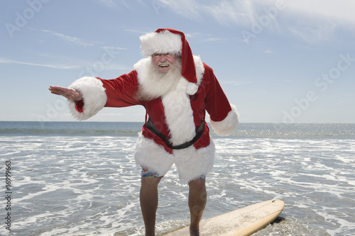 Father Christmas surfboards at the waters edge