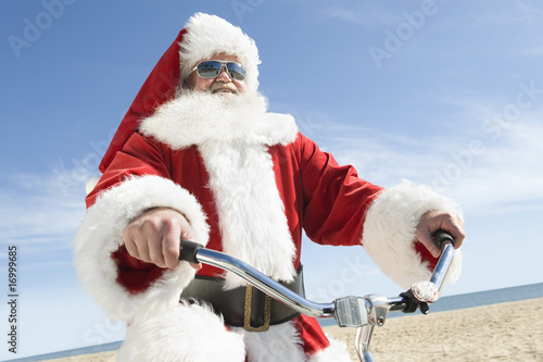 Father Christmas cycles along beach front